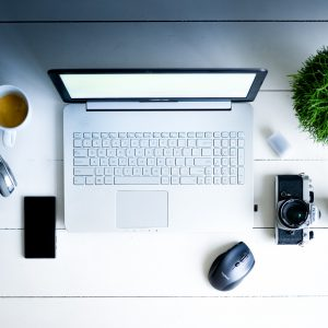 ordinateur entouré d'un cafe un casque, telephone, souris, appareil photo et plante