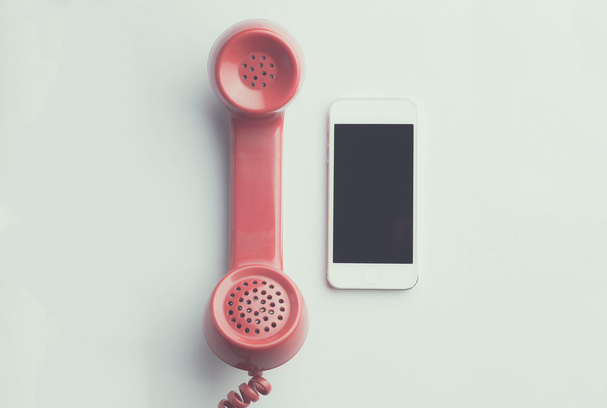 deux téléphones à côtés, un rose ancien, un smartphone récent