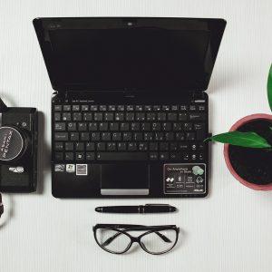 ordinateur entouré d'une plante d'une paire de lunettes d'un stylo et d'un appareil photo